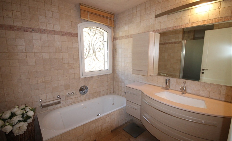 Bathroom with tan coloured tiles, a bathtub and a sink with a mirror over it