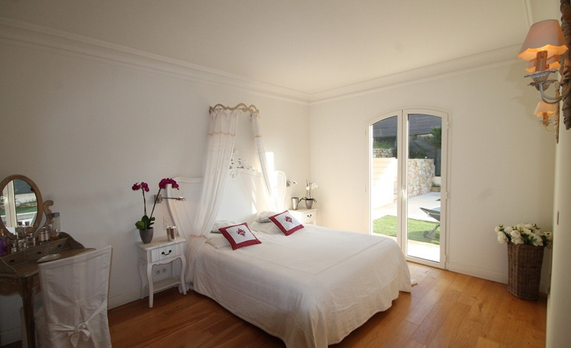 White double bedroom with wooden floor and dressing table in the corner in Cannes