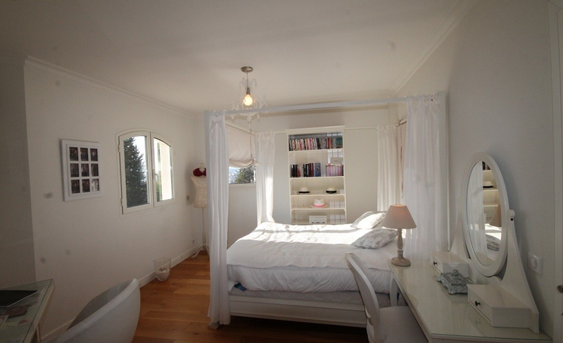 Canopy bed in a double bedroom with natural light coming from the window of a Cannes rental Villa