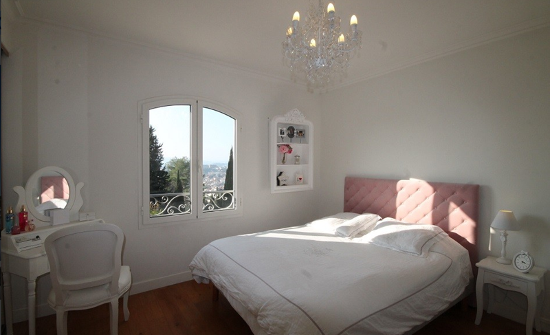 Double bed with a pink headboard, a window with views of Cannes and a white dressing table with chair in a corner