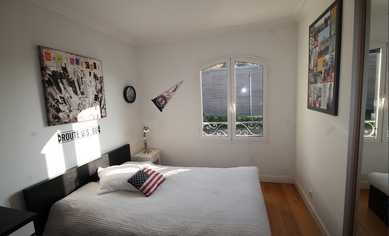 Double bed with a white blanket and a pillow with american flag on it in a Cannes villa