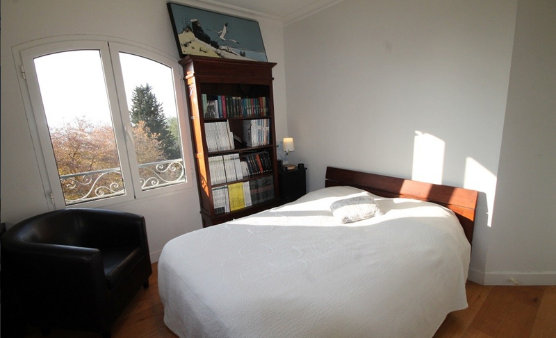 Double bedroom with a white blanket, a bookshelf along the wall and a black sofa in the corner