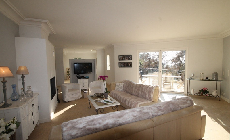 Living room with sand coloured couches, a flat screen tv and a door leading to outside sunny deck with table and chairs