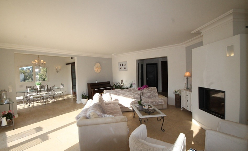 Living room with cream couches, a piano in the corner and a dining area in a Cannes villa