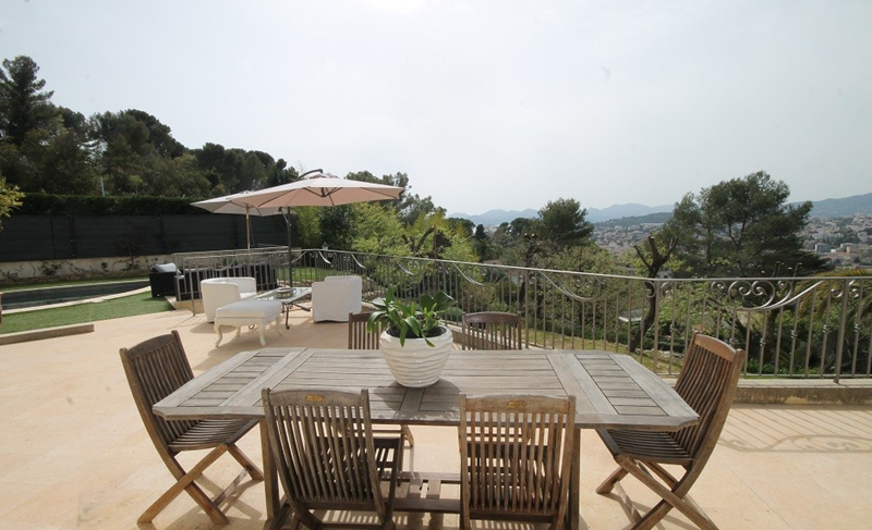 Outdoor seating area next to a garden and a swimming pool with views of city and nature in a north Cannes party Villa