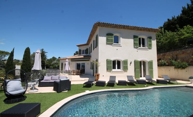 Swimming pool and garden with lounge chairs for sunbathing in a Cannes lions group Villa