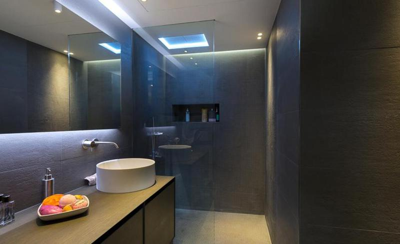 Bathroom with black coloured interiors, a sink and a standing shower separated by a glass door