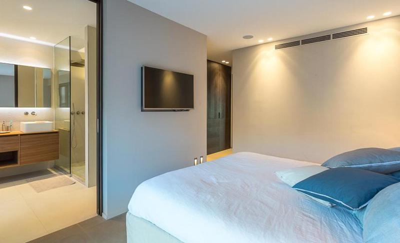 Double bed with white covers and blue pillows, facing a wall mounted tv in bedroom with attached bathroom