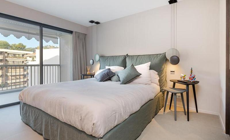 Double bed with green bed and cushions, cream covers and pillows and a glass door separating a terrace with Cannes views