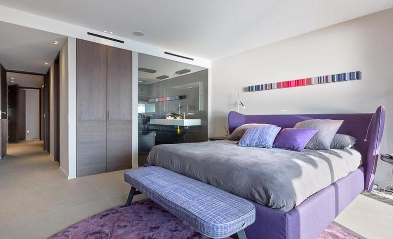 Double bedroom with a purple coloured bed and bench, natural light attached bathroom in Cannes