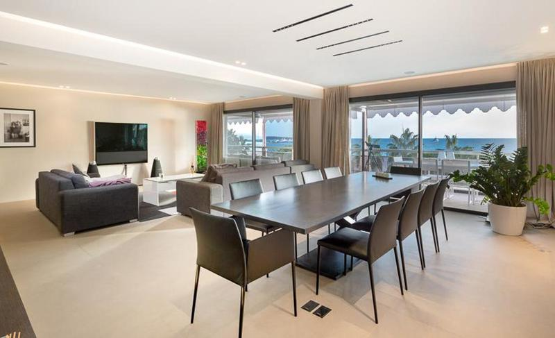 Open dining area with a black table and chairs and grey couches for meeting in a Cannes event apartment facing the sea