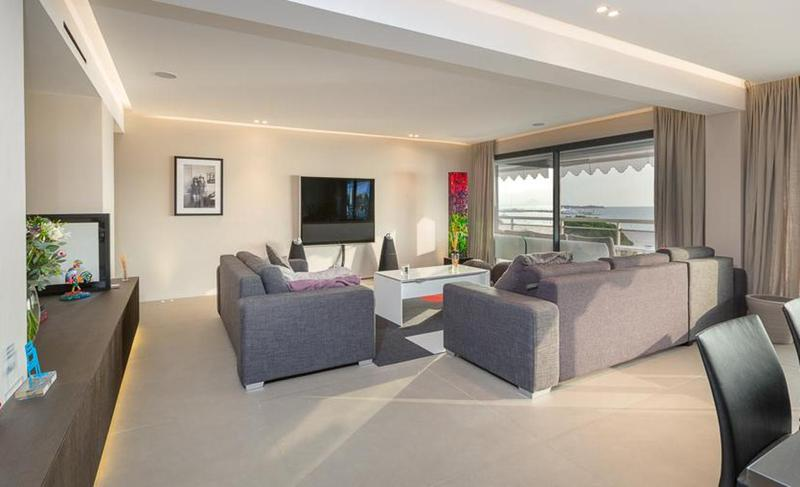 Living room with grey couches facing a flat screen tv, a colourful lamp in the corner and access to terrace in Cannes