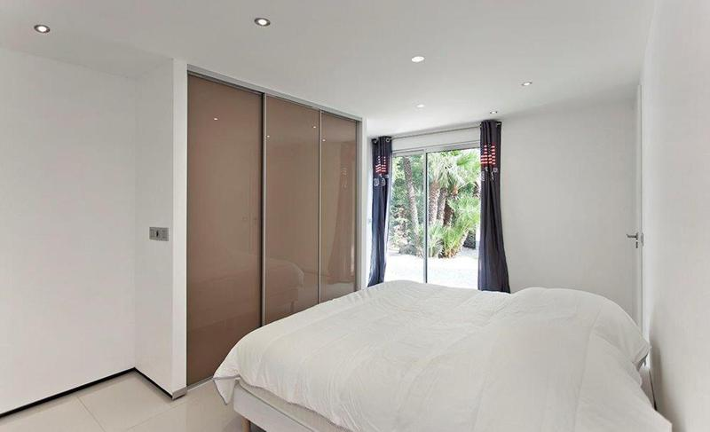 Double bedroom with a white blanket and access to outdoor garden