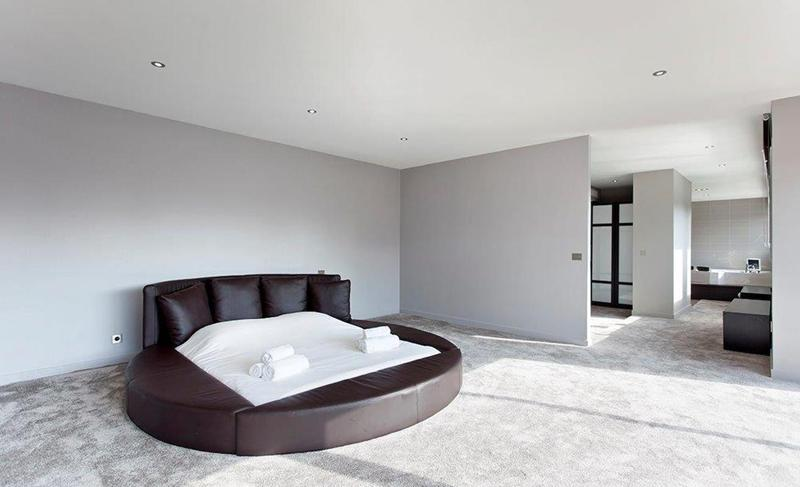 Brown circular couch in a spacious room with velvet carpet
