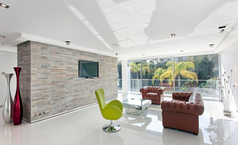 Marble flooring in the meeting room with a yellow revolvong chiar and a tv in a Cannes luxury villa for corporate groups