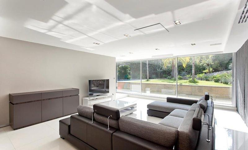 Brown leather couch in the tv room with glass walls offering outdoor garden views in a Cannes villa