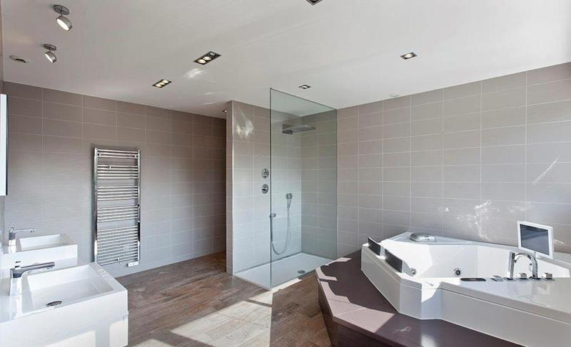 Glass-enclosed standing shower and a jacuzzi in the bathroom of a Cannes party villa