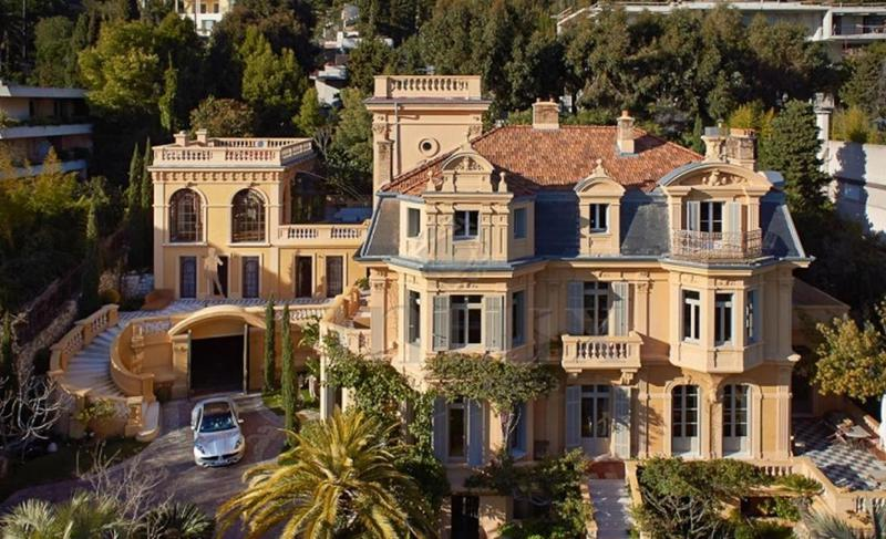 Villa front of a Cannes party mansion with gardens, pool and a car in the driveway