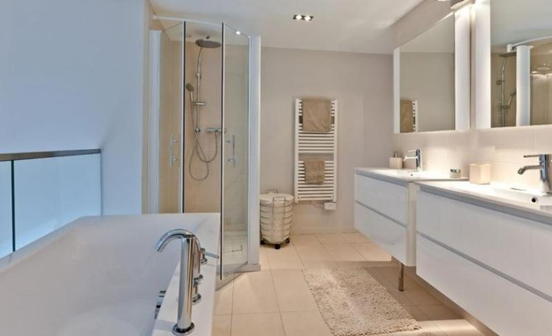 White bathtub, standing shower and dual sink in a Cannes rental penthouse