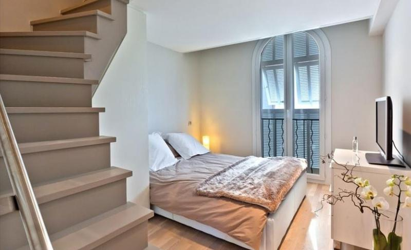 Double bedroom with folded velvet blanket, flat screen tv and stairs in Cannes