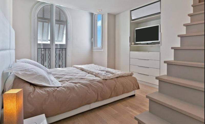 Double bedroom with stairs inside and a door to balcony