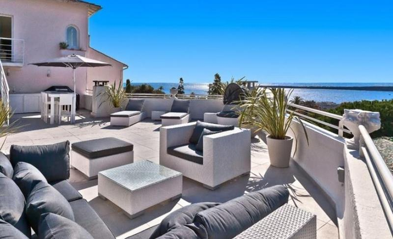 Sea views from a terrace of a Cannes group accommodation with couches and lounge chairs for sunbathing