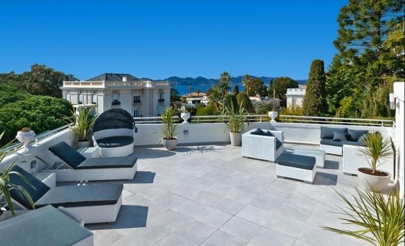 Lounge chairs and couches for sunbathing on a terrace in Cannes sea view penthouse for rent