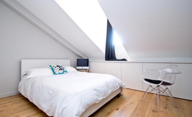 Double bed with white blanket and pillow in a room with a slanted ceiling in Cannes