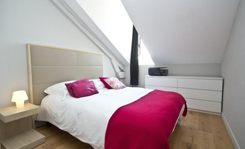 Double bedroom with a pink blanket and wooden floor
