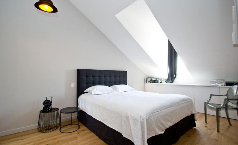 Black double bed with white covers and pillow on the wooden floor and a chair in the bedroom of a Cannes event apartment