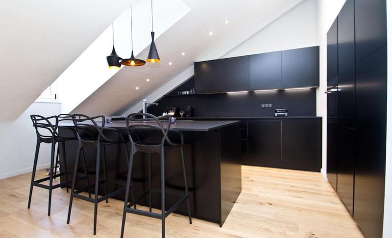 Black themed open kitchen with bar stools in a Cannes rental apartment