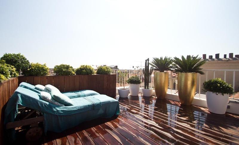 Wooden deck terrace with lounge chairs and a view of city in Cannes group accommodation