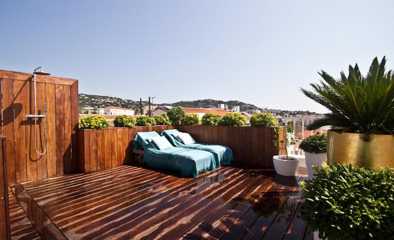 Wooden deck with shower, lounge chairs and plants on the terrace of a Cannes group event accommodation