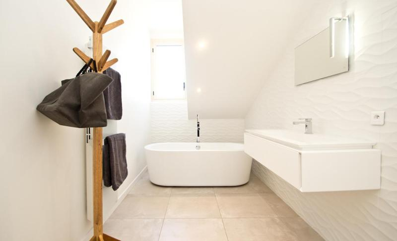 Soaking bathtub in a bathroom with white interiors and standing wooden hanger in Cannes rental apartment