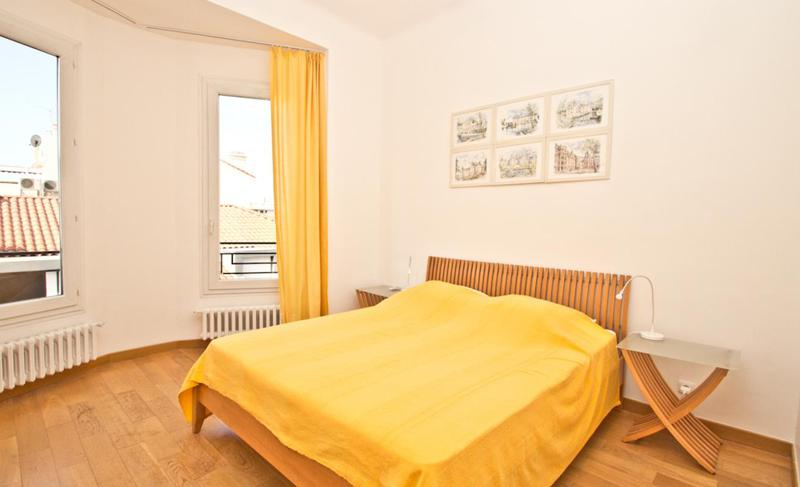 Wooden flooring in a bedroom with double bed, yellow blanket and curtains and a view of the city from 2 windows in Cannes