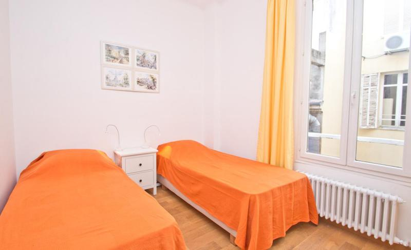 2 singles beds with orange blanket in a bedroom, a wall painting and a window