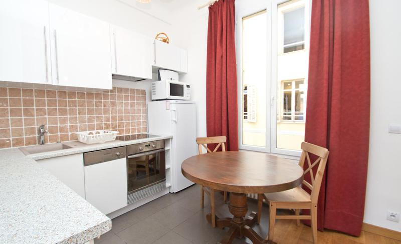 Round wooden table with 2 chairs in the kitchen with a fridge, a microwave and a door with red curtains