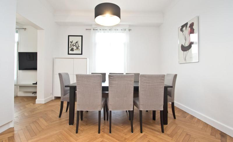 Dining table with chairs for meetings in a room with wall paintings in Cannes event apartment