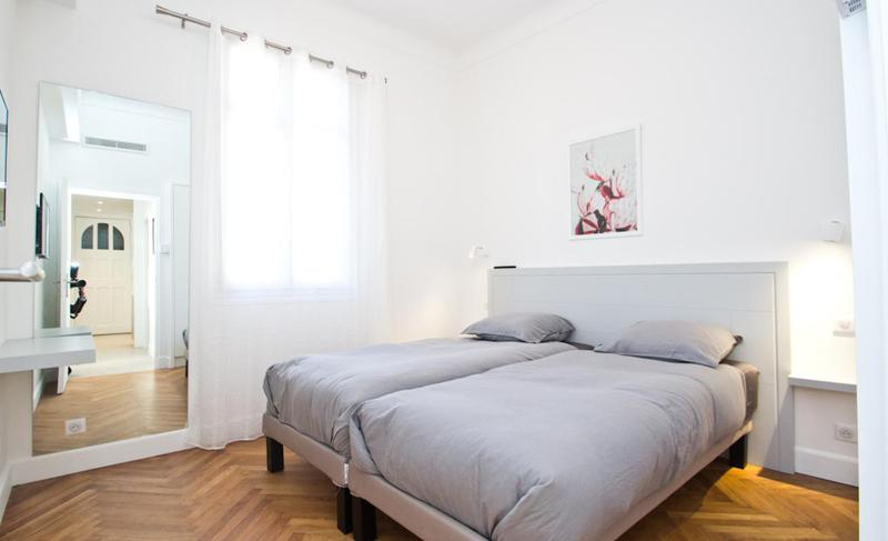 2 single beds in a bedroom with wooden floor, a large mirror and window covered by white curtains