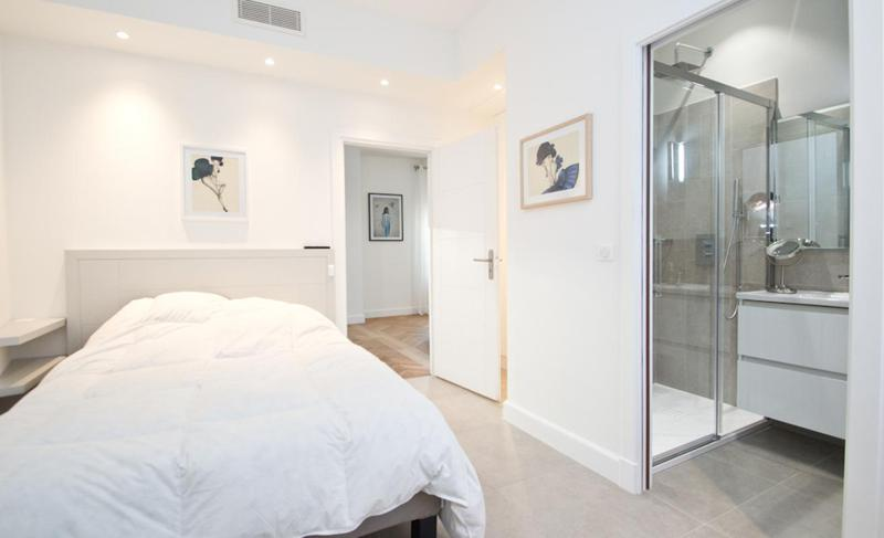Double bedroom with white interiors, blankets and attached bathroom with standing shower in Cannes group rental apartment