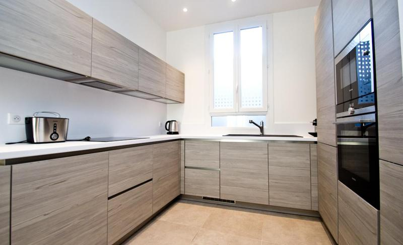 Kitchen with polished wooden cabinets, microwave, oven, induction stove, toaster and a window in Cannes rental apartment