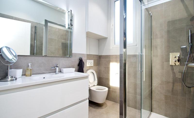 Bathroom with glass door standing shower, toilet and sink