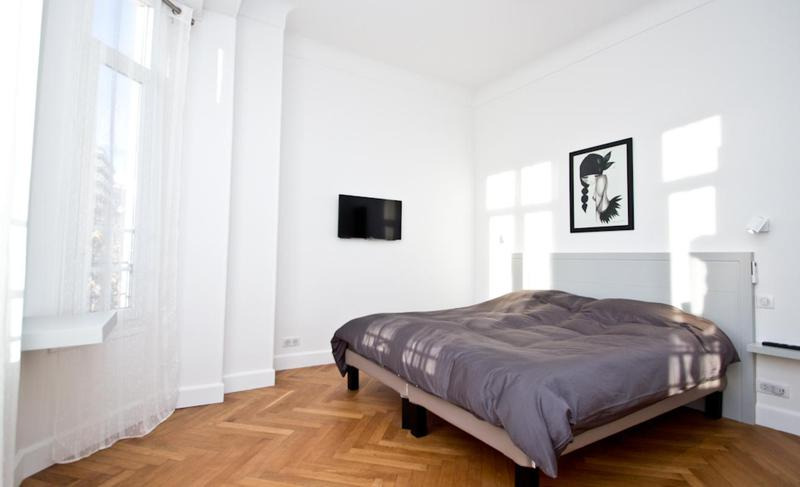 Double bedroom with natural light, brown blanket, a painting on the wall behind and flat screen tv on another wall in Cannes