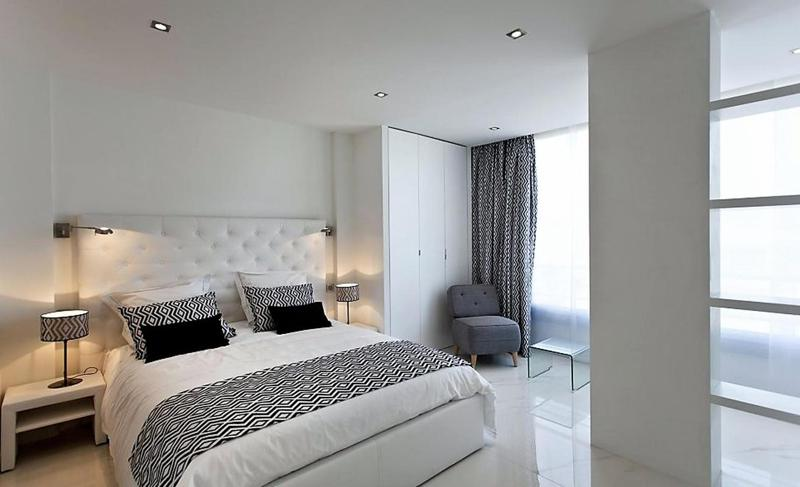 Bedroom with a double bed, white headboard, a closet and a grey coloured chair with a table in Cannes
