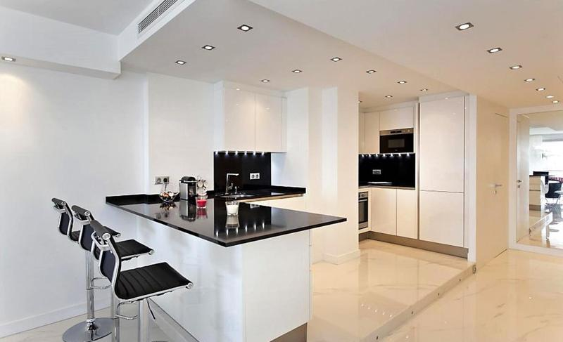 Black bar stools and countertop in a white themed open kitchen with coffee maker