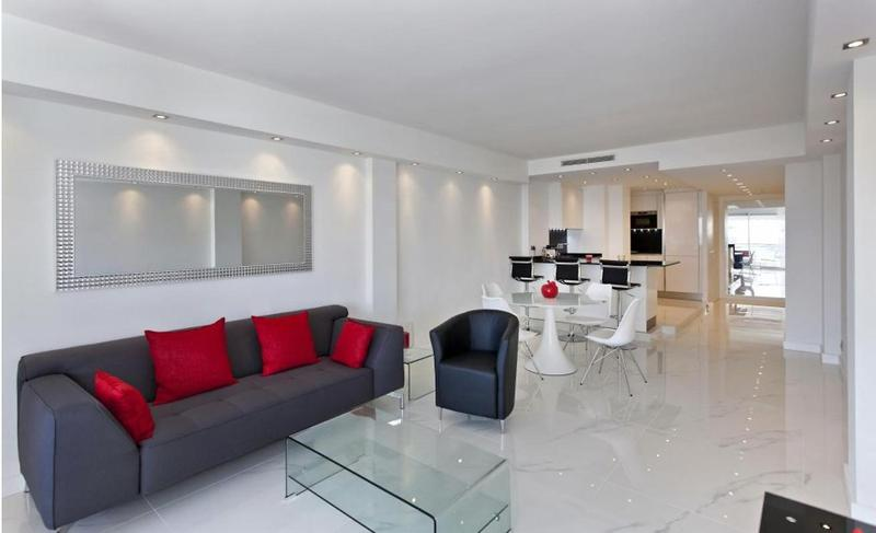 Couch with red cushions, a black sofa chair, open dining area and kitchen in the living room of a Cannes group apartment