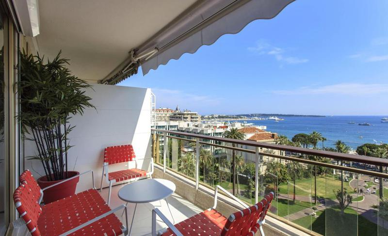 Red chairs and white table on the terrace of a Cannes rental apartment with sea views