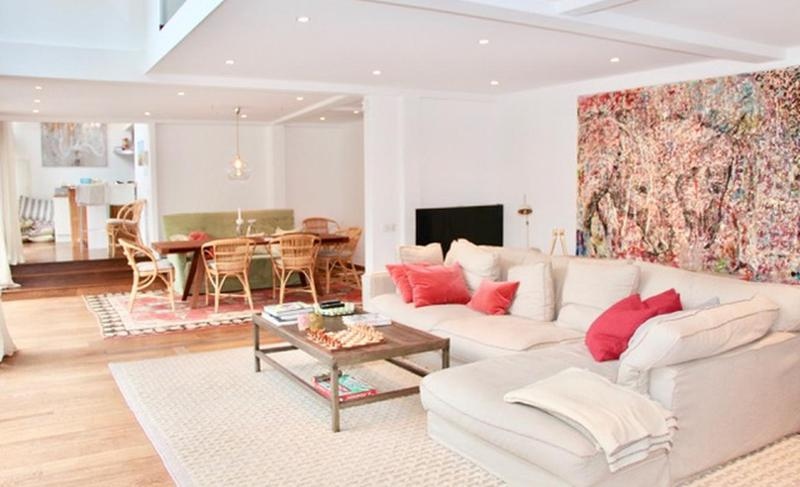 Living room with a cream couch and a dining area in a central Cannes villa on Rue d'Antibes