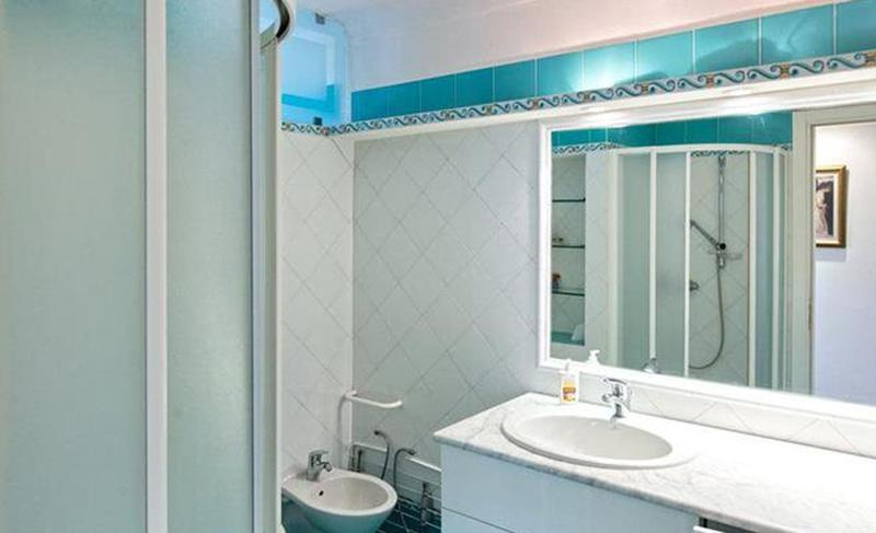 White and blue coloured tiles in a bathroom with a sink, a toilet and a standing shower