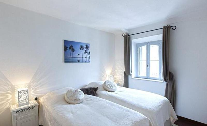 2 single beds in a double bedroom with a window and picture of palm trees in a Cannes apartment